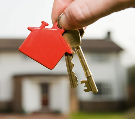 Photo of a hand holding house keys, with a house in the background