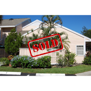A photo of the home at 200 Champions Way, with peach paint, a fence covering some palm trees and two parking spaces.